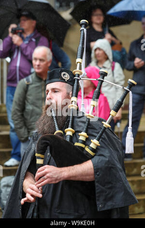 Glasgow, Scotland, UK. 14th Aug 2019. The 16th year of Glasgow's International Piping Festival continued with free concerts in Buchanan Street from an selection of Pipe Bands including Canadian and American enjoyed by 100's of spectators who were not put off by the heavy rain showers. Piper playing with the Islay Pipe Band Credit: Findlay/Alamy Live News - Stock Photo