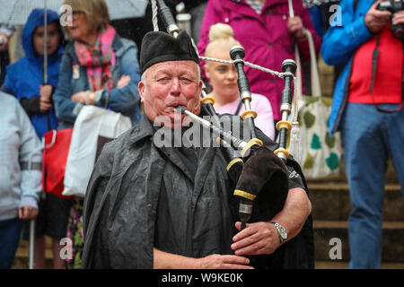 Glasgow, Scotland, UK. 14th Aug 2019. The 16th year of Glasgow's International Piping Festival continued with free concerts in Buchanan Street from an selection of Pipe Bands including Canadian and American enjoyed by 100's of spectators who were not put off by the heavy rain showers. JAMES McEACHERN playing with the Islay Pipe Band Credit: Findlay/Alamy Live News - Stock Photo