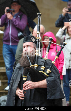 Glasgow, Scotland, UK. 14th Aug 2019. The 16th year of Glasgow's International Piping Festival continued with free concerts in Buchanan Street from an selection of Pipe Bands including Canadian and American enjoyed by 100's of spectators who were not put off by the heavy rain showers. Piper with the Islay Pipe Band Credit: Findlay/Alamy Live News - Stock Photo