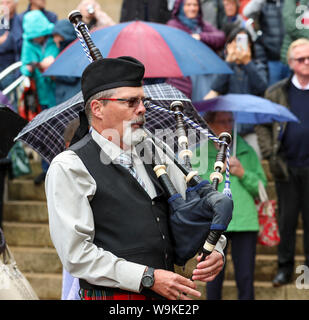 Glasgow, Scotland, UK. 14th Aug 2019. The 16th year of Glasgow's International Piping Festival continued with free concerts in Buchanan Street from an selection of Pipe Bands including Canadian and American enjoyed by 100's of spectators who were not put off by the heavy rain showers. Piper with the Grande Prairie and District Pipes and Drums, Canada Credit: Findlay/Alamy Live News - Stock Photo