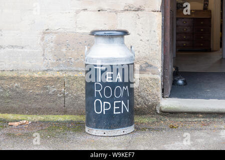 Traditional aluminium milk churn outside cafe used as sign saying 'Tea Room Open' in Abbey Terrace, Winchcombe,Gloucestershire,UK in the Cotswolds - Stock Photo