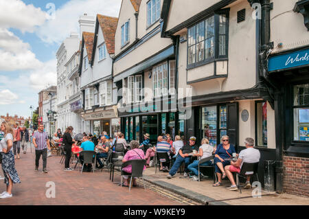 People sitting outside cafes in Court Street, Faversham, Kent. - Stock Photo