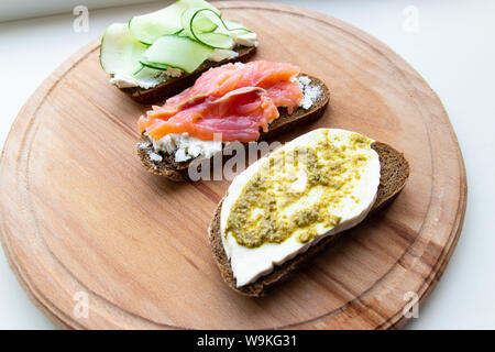 Food and proper nutrition concept. Tasty fresh sandwich with red fish, feta cheese cucumber and pesto on a pink ceramic plate on a wooden board - Stock Photo