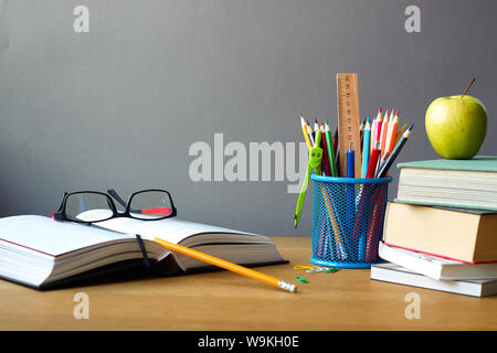 Back to school concept, school supplies, stack of books, green apple and open book with glasses on wooden surface, selective focus - Stock Photo