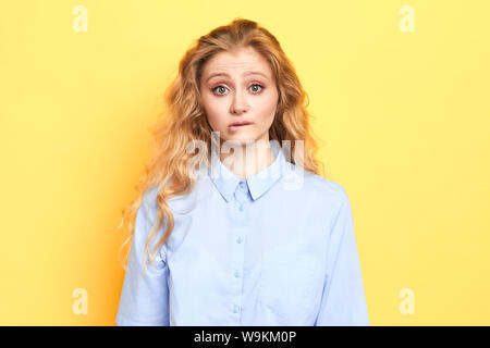 Shy and timid woman having indecisive confused look while answering to teacher's question in class, biting lips, feeling nervous, facial expression - Stock Photo