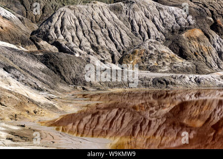 a pond - a lake or a river - with red water in a canyon among deserted sandy hills - Stock Photo