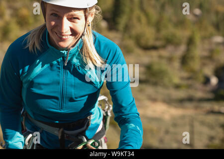 Portrait of rock climber preparing for climbing. - Stock Photo