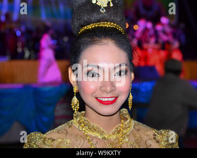 Dressed-up Thai girl wears a golden Lanna-style lace dress and elaborate hairdo with hair jewellery and drop earrings during a rural Yi Peng parade. - Stock Photo