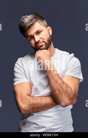 happy handsome bearded young man touching his chin,looking at the camera. indoor studio shot, isolated on gray background.closeup portrait. - Stock Photo