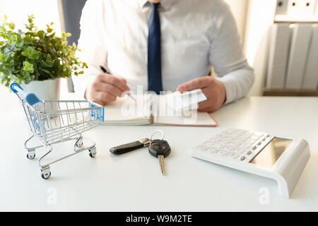 Businessman calculating shopping expenses for car purchase, holding receipts in hand. Empty shopping cart and car keys in front - Stock Photo