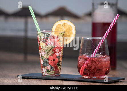 Photo detail of a tropical juice next to a red cocktail served in a robust glass on a black stone tablet with a bottle in the background out of focus. - Stock Photo