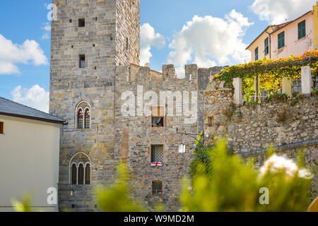 local Italian woman leans out from a window on the ancient city gate of the town of Portovenere, Italy, part of the Italian Riviera in Liguria - Stock Photo