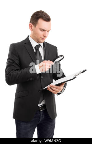 A portrait of a young businessman looking at a document on a clipboard through a magnifying glass, isolated on white background. - Stock Photo