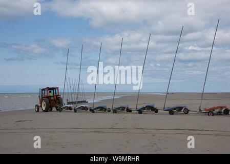 A tractor pulling 9 linked sand yachts, without sails, on to the beach in preparation for a competition - Stock Photo