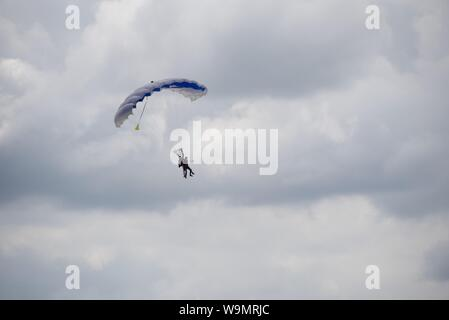 A tandem parachute jump with a clearly visible selfie stick being used - Stock Photo