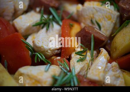 Chicken, chorizo, chopped tomatoes red pepper, onion, potato wedges with Rosemary and Thyme stir fried in olive oil before going into the oven - Stock Photo
