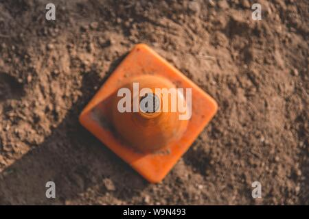 An overhead closeup shot of a traffic cone on a sandy surface - Stock Photo