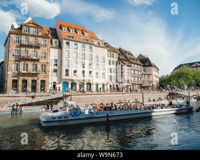 Strasbourg, France - Circa 2019: Strasbourg famous promenade pedestrian street Quai des Bateliers with half timbered houses and people disembarking Batorama boat in port Stock Photo