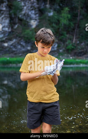 Mobile phone screen care, little boy washes a smartphone with river's water and lather. The child flooded phone with water and disabled it. - Stock Photo