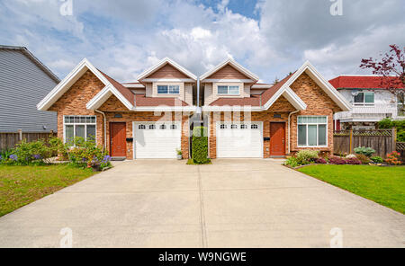 Residential duplex building with concrete drive way and green lawns in front - Stock Photo