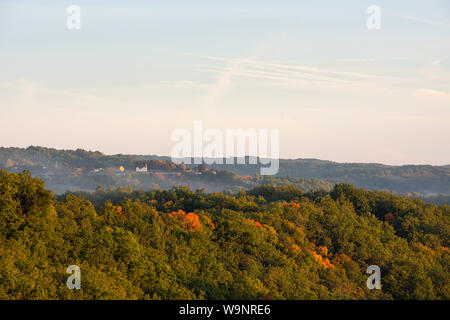 Morning mist rises over a dense forest in the Perigord region of France - Stock Photo