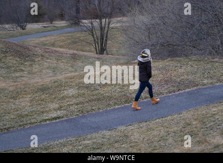 Young woman in cold weather gear taking a walk in the park despite the freezing temperature. - Stock Photo