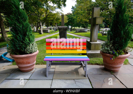 A bench painted in the style of Gilbert Baker's Pride Flag, located at St. Paul's On the Green, Norwalk, CT - Stock Photo