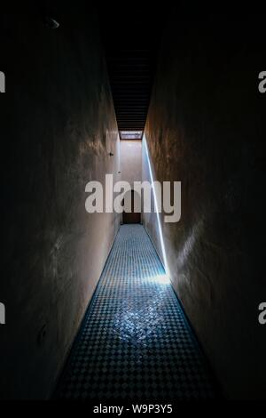 Vertical shot of an empty hallway with a brown door in the distance