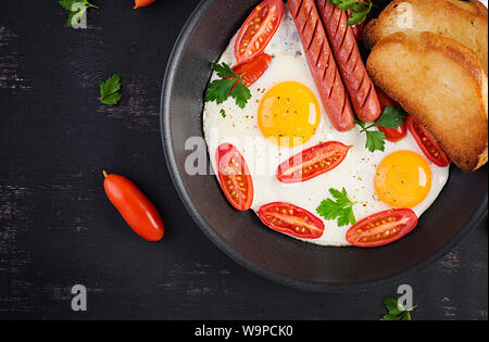 English breakfast - fried egg,  tomatoes, sausage,  and toasts. Top view, overhead - Stock Photo