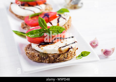 Sandwiches with mozzarella, tomatoes and rye bread on white wooden table. - Stock Photo