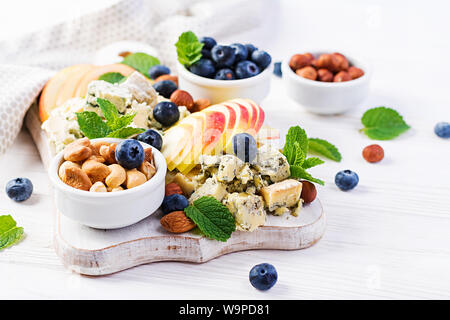 Cheese platter with assorted cheeses, blueberry, apples, nuts on white table. Italian cheese  platter and fruit. - Stock Photo