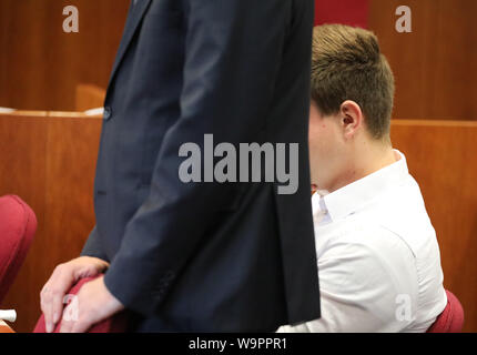 Bonn, Germany. 15th Aug, 2019. There's a cop in the dock crying. After a deadly shot at a colleague, the trial against a young policeman has begun before the Bonn Regional Court. The accused is said to have mistakenly assumed during a gun training that he had a training weapon in his hand instead of a sharp service weapon (parts of the picture were made unrecognisable for reasons of personal rights). Credit: Oliver Berg/dpa/Alamy Live News - Stock Photo