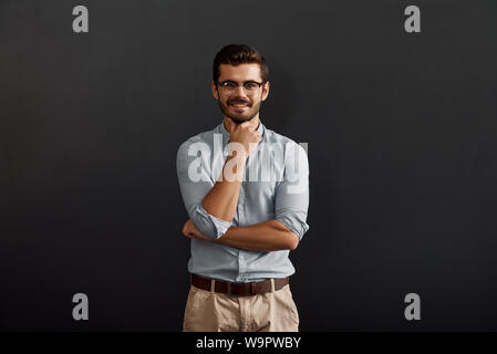 Handsome businessman. Happy young bearded man looking at camera and touching his chin while standing against dark background. Work concept. Studio shot - Stock Photo