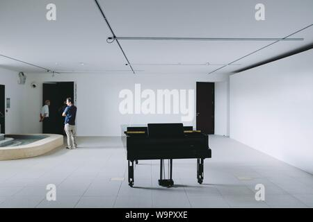 A black large piano in a white room with people around - Stock Photo