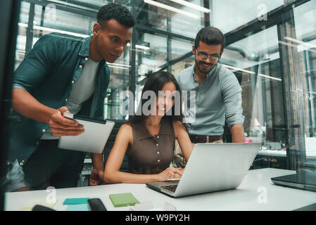 Business people. Group of three young and cheerful employees using modern technologies while working in modern office. Job concept. Workplace