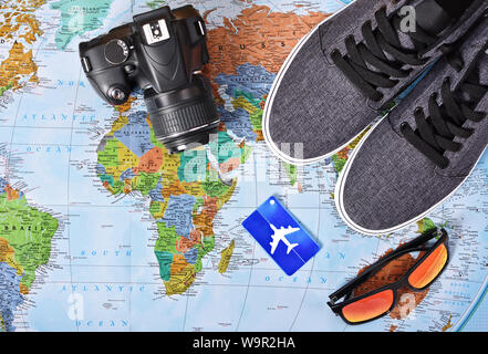 Top view of camera, airplane luggage tag, sunglasses and sneakers on a map of the world. These are my travel essentials for a trip around the world or - Stock Photo