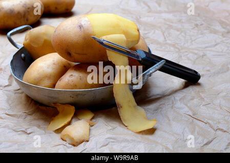 peeling potato with potato peeler - Stock Photo
