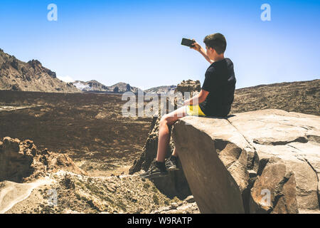 Teenager male enjoying outdoors sitting on a mountain cliff overlooking the Tenerife Teide National Park, Spain. Young boy making video for social - Stock Photo
