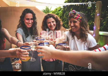 Group of happy friends cheering with glasses at dinner outdoor in terrace. Teenager and mothers having fun while drinking and eating. Focus on glasses - Stock Photo