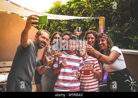 Happy friends taking photo with smartphone at barbecue party. Young people doing appetizer outdoor drinking wine and alcohol free drinks. Technology t - Stock Photo