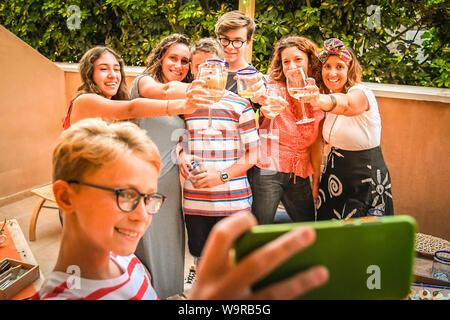 Happy friends taking photo with smartphone at barbecue party. Mothers and sons doing appetizer outdoor drinking wine and alcohol free drinks. Technolo - Stock Photo