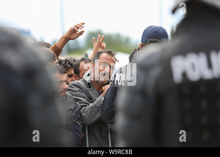 Bregana, Slovenia - September 20, 2015 : The police choosing syrian refugees from the crowd to take them to the bus one by one on the slovenian border - Stock Photo