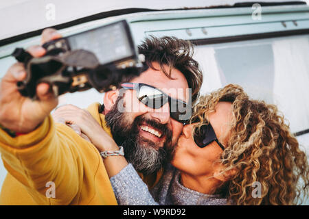 Happy kissing couple taking selfie together  with vintage van in background. Husband kiss her wife making social video with camera to share online wit - Stock Photo