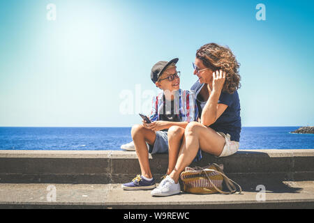 Smiling mother and son watching smartphone together sitting near the sea. Woman and trendy young boy playing with cell phone. Happy family enjoying