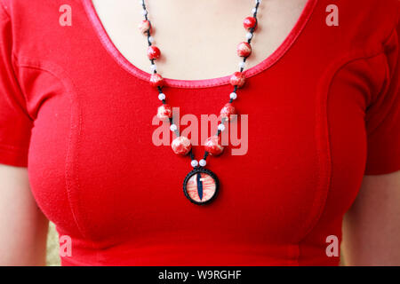 dragon red eye cabochon and ceramic beads. necklace on a young girl on a red background. Amulet - Stock Photo