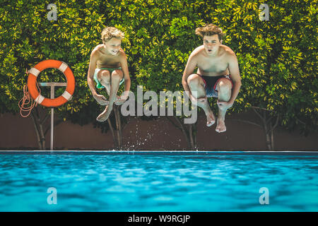 Two young boys having fun diving into the swimming pool.View from the water of happy teenagers jumping in. Tourist people enjoying summer holiday - Stock Photo