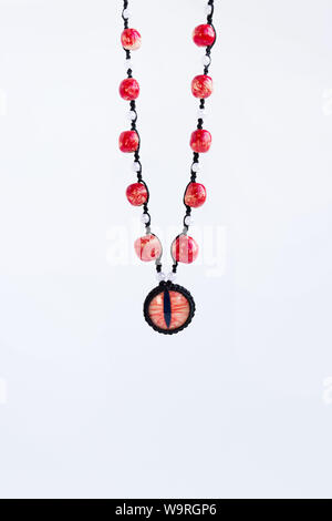 dragon red eye cabochon and ceramic beads on a white background. Amulet - Stock Photo