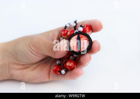 dragon red eye cabochon and ceramic beads in a girl s hand on a white background. Amulet - Stock Photo