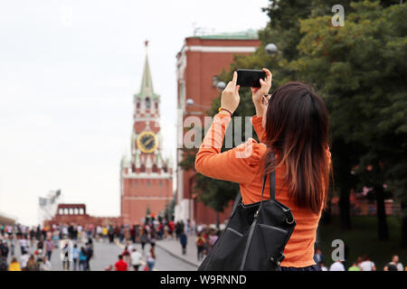 Woman tourist taking pictures of Moscow Kremlin on smartphone in summer. Crowd of tourists on the Red square, travel in Russia - Stock Photo