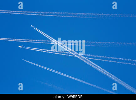A lot of passenger airplanes on the air, busy air traffic, traveling high season starts concept. White planes against blue sky.  Photo manipulation. - Stock Photo